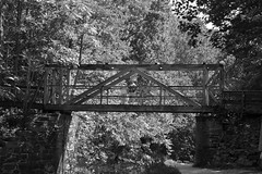 a bridge over calm waters (jakarachuonyo) Tags: bridge autumn blackandwhite reflection iso100 maryland cocanal greatfallsnationalpark focallength50mm aperturef28 canonrebelxti lenstamronaf1750mmf28 shutterspeed1200sec washingtonphotographymeetupgroup