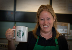 A welcome face at the end of a long journey #27 of 100 (r c hill photography) Tags: street portrait green coffee smile canon starbucks mug fillflash welcoming 30d whiteley speedlite ef50mmf14usm 430ex 100strangers