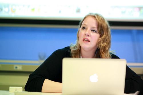 Hiranthi achter bureau en laptop kijkend naar publiek