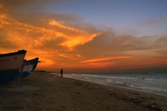 Fire and the fisherman (dubey) Tags: sunset beach clouds canon boats evening fisherman dramaticsky pondicherry ixy55 noobshots