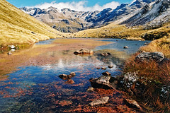 Lunch time (Daniel Murray (southnz)) Tags: tarncol edwardshawdonroute tarn reflection mountain snow tussock tramping trekking hiking southisland nz newzealand eos50escanfromprint southnz landscape scenery