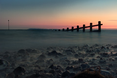 Sunset Defense (stevec77) Tags: uk longexposure sunset sea england sky mist beach water fence d50 landscape twilight rocks waves westsussex dusk pebbles nikond50 foam isleofwight selsey englishchannel breakwater specland