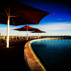 shade (hoogen imagery) Tags: blue red water umbrella australia victoria geelong easternbeach coriobay hoogenimagery auselite