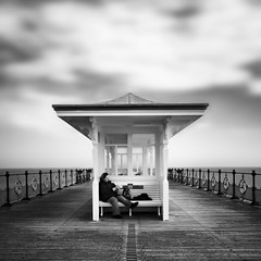 Read A While (Andy Brown (mrbuk1)) Tags: wood longexposure sea sky woman cloud person reading mono book pier blackwhite still sitting floor candid seat horizon symmetry dorset shelter railings swanage ironmongery
