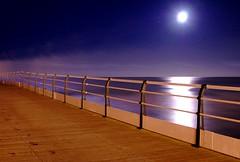 Shimmering (~Glen B~) Tags: uk sea england moon night reflections coast pier still britain cleveland shoreline eerie calm boardwalk moonlight railing teesside stillness saltburn redbubble:id=2708821shimmering