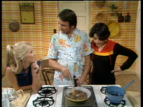 Jack Tripper cooks while Janet and Chrissy watch