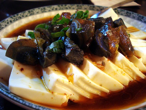 Several thick slices of silken white beancurd lie in a dish, with chopped amber/black/dark green century egg on top.  A thin translucent brown sauce based on soy sauce and sesame oil has been poured over and around.
