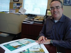 Terry Fallis poses with cover artwork for his book