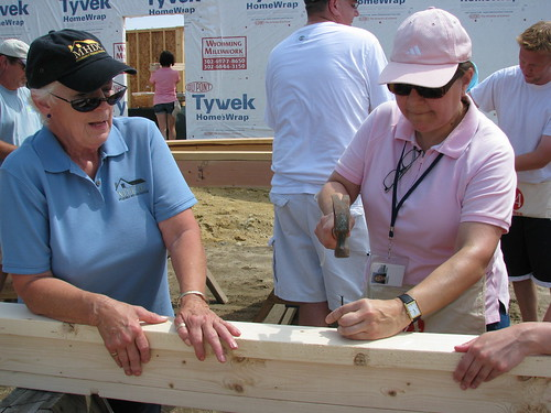 Peggy Gallego, Milford Housing Development Corporation and USDA Housing Administrator Tammye Trevino (Right) take turns at building walls for Suzanne and Dennis Passwaters new home.