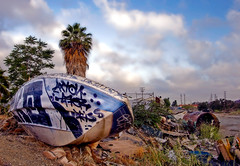 Abandoned Ship! (G60Pulse) Tags: road street blue sky urban abandoned clouds trash canon graffiti boat losangeles garbage weeds alley junk rust cityscape cloudy filter palmtree bow vacant spraypaint hull polarizer tagging interestingness245 i500 colorphotoaward superbmasterpiece