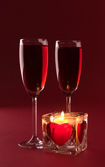 Wineglasses and candle on the white background (shadphotos) Tags: lighting light red holiday love church glass sign yellow night drunk dark fire day candle heart bright wine symbol crystal drink ghost beverage decoration nobody scene valentine romance illuminated winery celebration flame alcohol meditating glowing wax candlelight spirituality wineglass figurine liquid tranquil candlestick elegance fragility