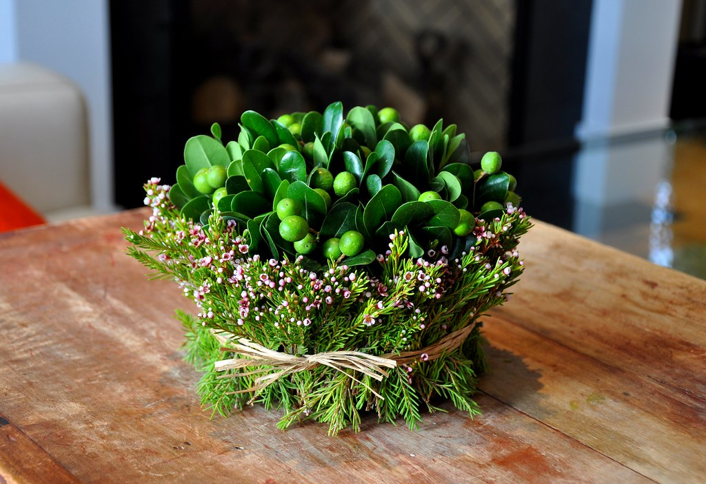 a floral arrangement with heather chinaberries and pittosporum