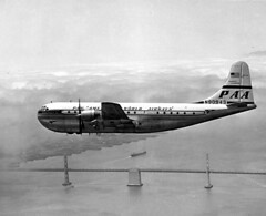 Pan American Airways Boeing 377 Stratocruiser over San Francisco-Oakland Bay Bridge (UW Digital Collections) Tags: airplanes bridges baybridge sanfranciscobaybridge oaklandbaybridge panamericanairlines panamericanworldairways commercialairplanes boeingairplanes boeing377stratocruiser