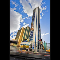 take me away [HDR - Kuwait City] (alvin lamucho ) Tags: longexposure morning motion bus colors buildings movement angle flag perspective panasonic posters billboards kuwait 1022mm hdr bold kuwaitcity upward takemeaway oppositesideoftheroad alvinlamucho verticalwideangle