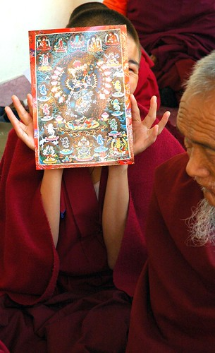 Happy young monk, with a photo of Hevajra, Sakya Lamdre, in the Tharlam Monastery of Tibetan Buddhism courtyard, shows a photo of Hevajra, Boudha, Kathmandu, Nepal 7149
