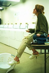 Sabrina's Wash Load Waiting (neohypofilms) Tags: light woman white cold color cute slr film girl beauty fashion female 35mm vintage hair fun photography shoes waiting mood phone basket sweet candid hipster cell style atmosphere retro teen negative laundry photograph teenager clogs ambient heels series casual concept machines conceptual mules washers slippers platforms dryers perforated sweather neohypofilms