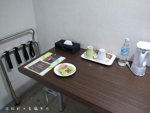 成旅晶贊豪華房辦公桌上茶杯水壺與小點心