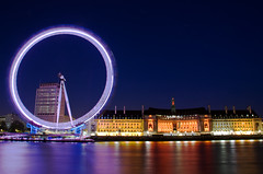 The London Eye at Night (Jim Boud) Tags: uk longexposure travel blue red orange reflection building london water colors yellow thames canon river eos colorful europe purple nightshot unitedkingdom dusk smooth londoneye milleniumwheel landmark southbank ferriswheel dslr riverbank digitalrebel photoart digitalslr xsi nightexposure slowshutterspeed artisticphotography eos450d jimboud kissx2 topazadjust jamesboud