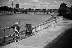 Dancing with the wind (Mieszko Stanislawski) Tags: street old people bw woman river blackwhite wind pavement poland krakow skirt elderly riverbank vistula wisla whitehair krakoff podgorze