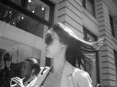 slick (redjoe) Tags: street nyc newyorkcity windows urban woman building beautiful sunglasses hair walking spring movement raw wind walk manhattan candid midtown breeze redjoe joehorvath
