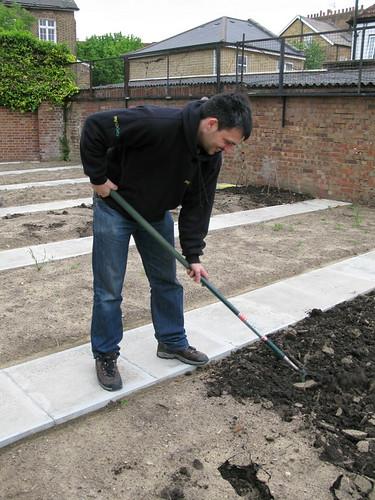 Under gardener hoeing