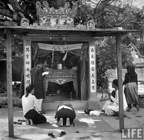 Hanoi 1948 - Natives observing a service in small Buddhist temple.