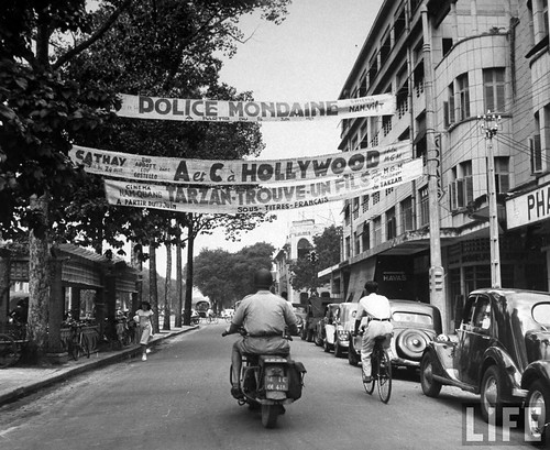 Saigon 1948 - Typical street in Saigon, with cyclists and Tarzan movie advertising at local theatre.