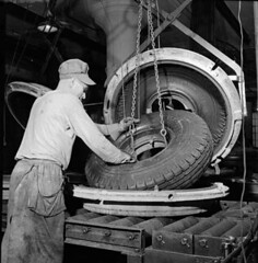 Workman removes a synthetic rubber tire from t...
