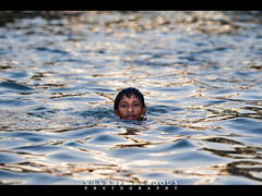 Buriganga Swimmer Bangladesh (Shabbir Ferdous) Tags: light boy portrait female river garbage afternoon photographer shot swimmer littlegirl dhaka waste bangladesh bangladeshi buriganga ef70200mm28lisusm burigonga shabbirferdous canoneos1dmarkiv wwwshabbirferdouscom shabbirferdouscom