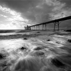 Clevedon Pier III (Adam Clutterbuck) Tags: ocean uk greatbritain sea england blackandwhite bw seascape beach monochrome square landscape mono coast pier blackwhite rocks waves victorian wave somerset bn boulders coastal shore elements gb blogged bandw sq surge limitededition clevedon northsomerset greengage adamclutterbuck sqbw bwsq showinrecentset shortedition le50 limitededition50