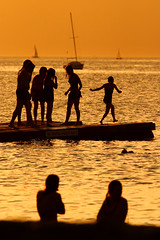 summer (♫ marc_l'esperance) Tags: ocean park light sunset summer orange reflection beach water kids vancouver canon fun boats eos gold golden evening jumping warm raw sailing © platform silhouettes floating reflected 10d jericho nocrop allrightsreserved shimmering 2007 cml gvrd canonef70200mmf28lusm canon70200f28l ucropped canonextender2x
