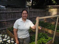 Adriana stands in front of her raised bed garden