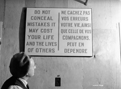 "Woman worker reads poster, ""DO NOT CONCEAL MISTAKES IT MAY COST YOUR LIFE AND THE LIVES OF OTHERS"" at the Cherrier bomb-making plant. /  l'usine de fabrication de bombes Cherrier, une ouvrire lit une afficheprvenant les ouvriers de ne pas dissimuler le (BiblioArchives / LibraryArchives) Tags: woman canada poster montral quebec montreal wwii lac canadian worldwarii qubec worker canadians canadiens 1941 affiche canadien bac secondworldwar canadienne libraryandarchivescanada canadiennes deuximeguerremondiale ouvrire bibliothqueetarchivescanada nicholasmorant cherrierbombmakingplant usinedefabricationdebombescherrier"