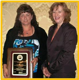 Christal Stidham (left) and Tina Richardson, USDA Rural Development Area Technician for the Indiana North Vernon Area Office, celebrate Tuesday's award presentation.