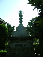 Statue (Saw You On The Flipside) Tags: flowers japan temple tokyo shrine stones cemetary pots   markings tombs engravings  kiyose