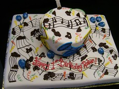 A music-themed cake  with chocolate music notes and cut-out musical instruments