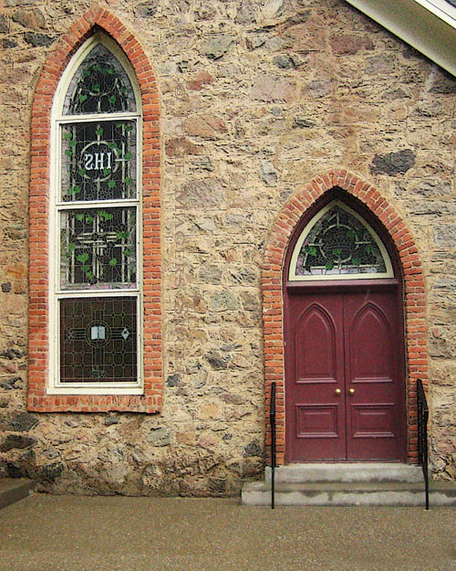 A charming stone Gothic church with burgundy doors and a stained glass window under brick arches.