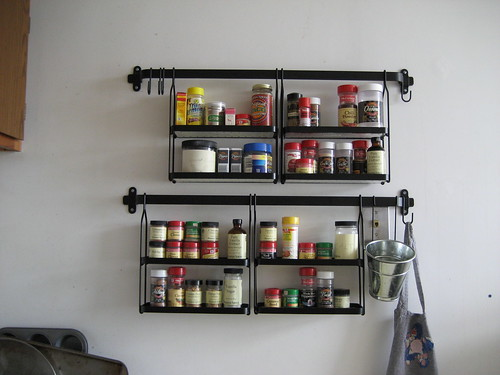 A wooden spice rack could be a shelf or take the whole door or wall. Some  of the wooden spice racks might be painted and have nice decorations.