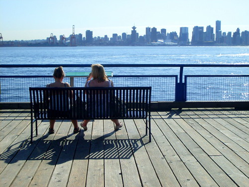 Lonsdale Quay in North Vancouver, two woemn sit on a bench at the boardwalk overlooking downtown Vancouver and Coal Harbor across the water
