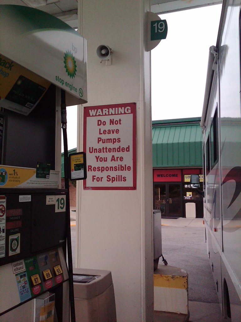 gas station sign, do not leave pumps unattended, oil spill,