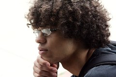thinker (emily_chiavelli) Tags: boy portrait people white black person glasses hand steel jaw afro think fingers thinker tshirt fist thinking backpack africanamerican adamsapple mulatto