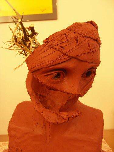 Sculpture en terre figurative et surréaliste vue de ¾ représentant une tête de Christ dont le visage, recouvert de bandelettes, est découpé et creux, avec un morceau de couronne d'épines – Sandrine Vallée