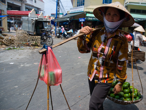 Woman carrying a yoke in Hanoi, Vietnam