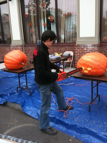 Skunk carving a pumpkin with a chainsaw