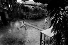 rain. (TiMm1) Tags: travel bw film rain kids philippines documentary hp5