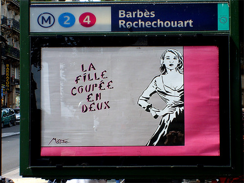 "stencil graffiti from Miss.Tic: An image of a woman in a full-skirted, 50s style dress with princess neckline, one hand on her hip, to the right of the words, ""la fille coupee en deux"""