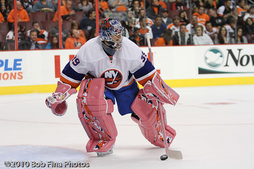 Rick DiPietro #39 of the New York Islanders,  while wearing pink goalie equipment to help raise awareness and money for Hockey Fights Cancer, plays the puck to the side of the net while playing agains