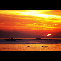 blazing away (DocTony Photography) Tags: ocean sunset sea orange sun mountain water yellow gold bay twilight bravo ship searchthebest horizon philippines manila serene manilabay relfection bff eow magicdonkey supertony outstandingshots artlibre henyo superaplus aplusphoto ultimateshot superbmasterpiece infinestyle doctony