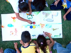 top view of six children painting together on the same table the table is on grass