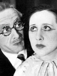 A close-up of Paula Maxa looking melodramatic next to a man in spectacles